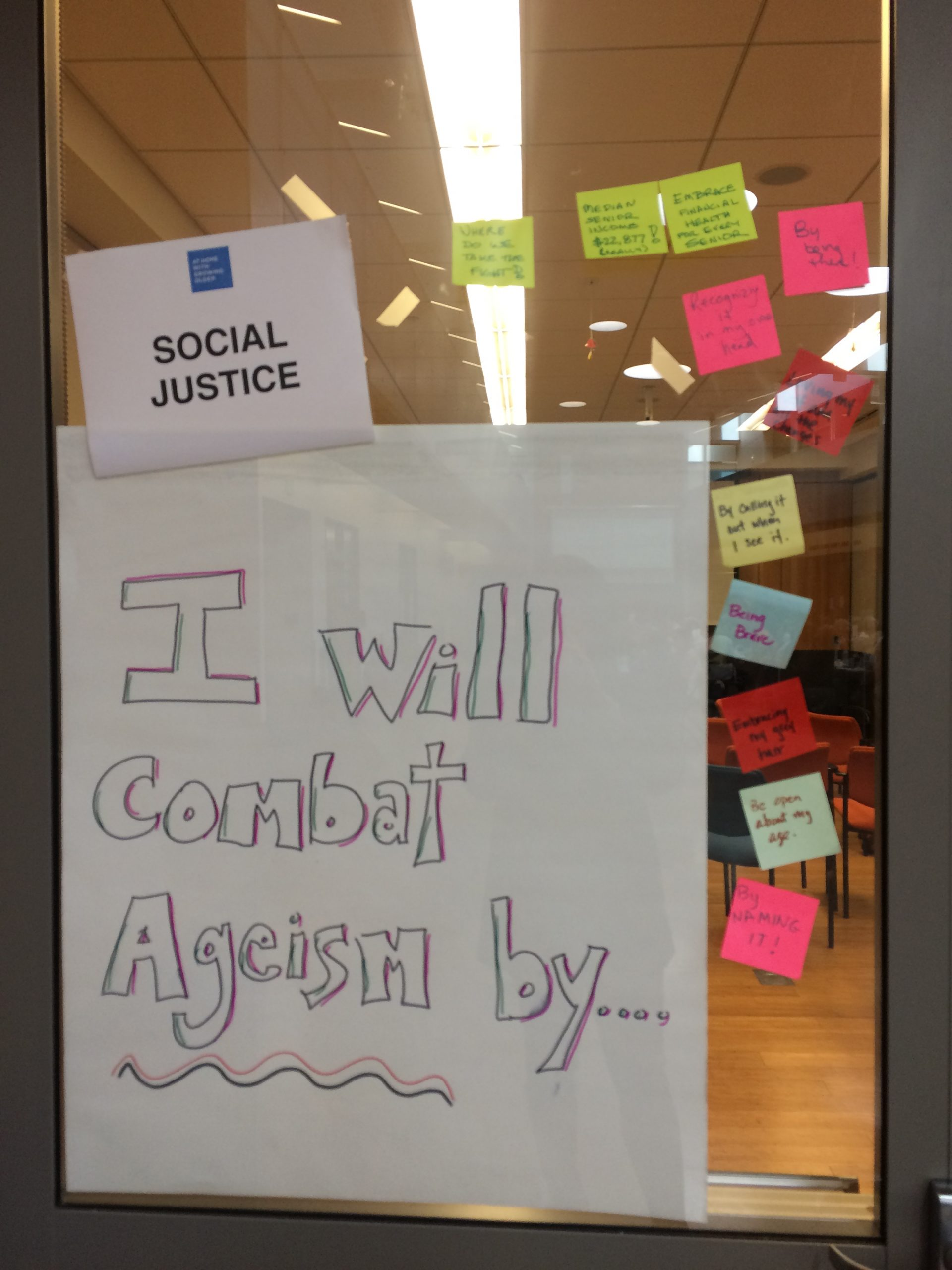 "Interactive activity titled ""I will combat ageism by…"" written on poster paper. Participants provided sticky notes finishing the sentence."