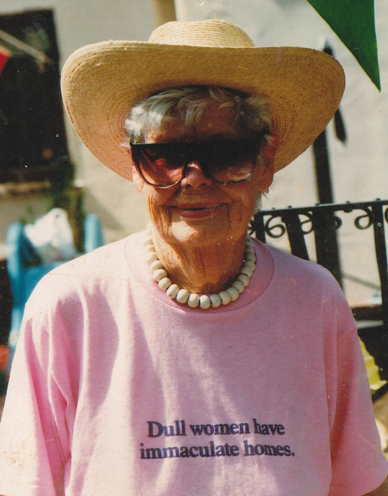 "Jean smiling, wearing a pink shirt that reads, ""Dull women have immaculate homes."""