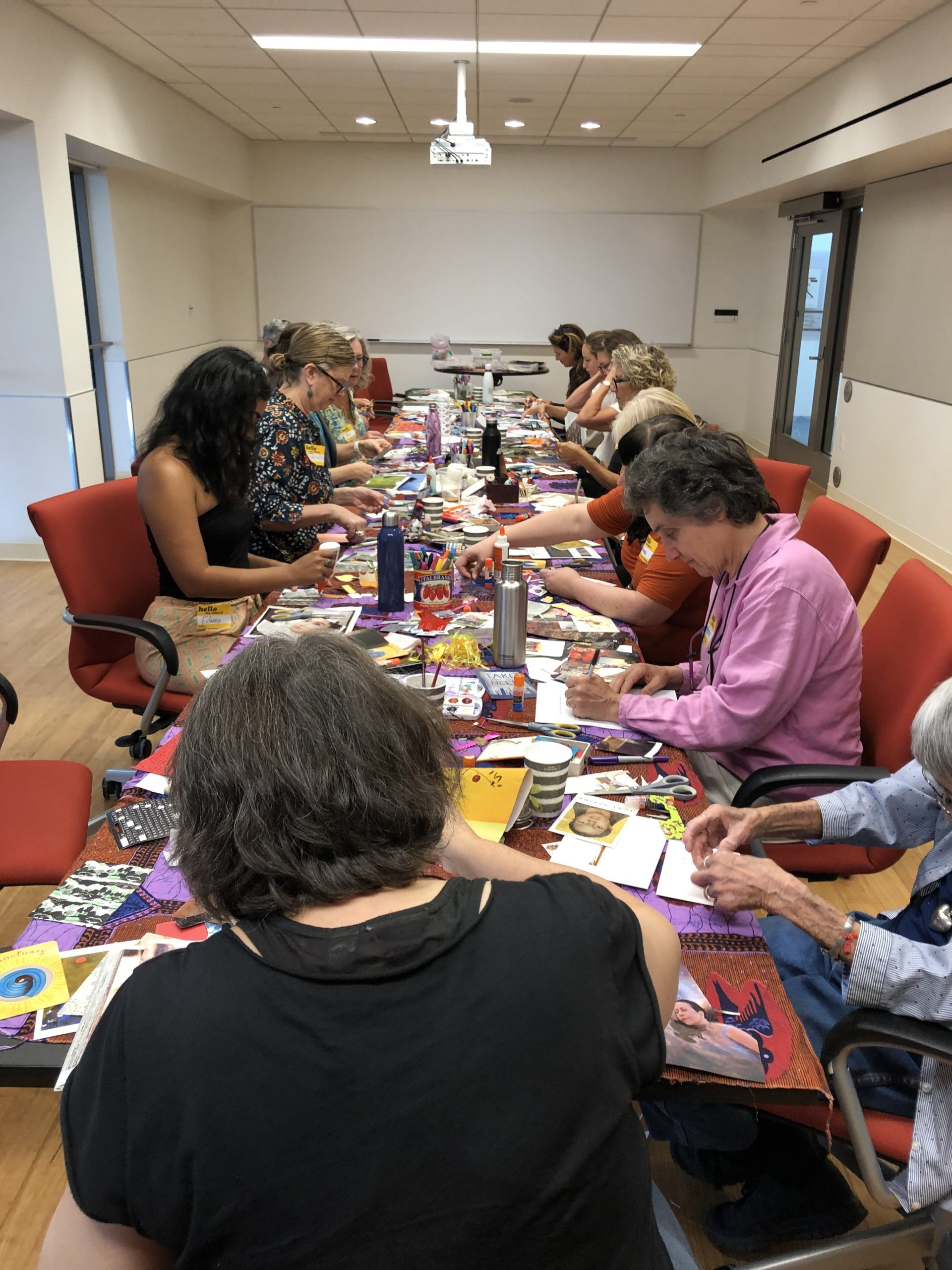A group of women seated at a long conference table, making postcards with collage materials.