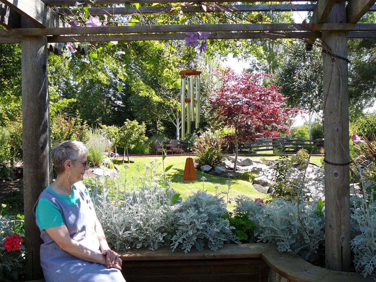 Picture of a mature woman seated near a lovely landscaped garden.